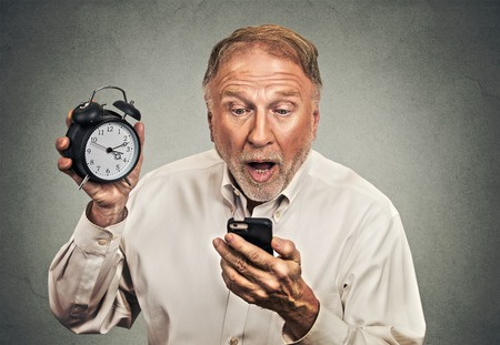 reminder concept: Portrait surprised business man with alarm clock looking at smart phone with funny face expression late for meeting isolated grey wall background. Human face expression emotions, feelings