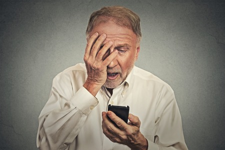shock: Upset stressed man holding cellphone disgusted shocked with message he received isolated on grey background. Funny looking human face expression emotion feeling reaction life perception body language