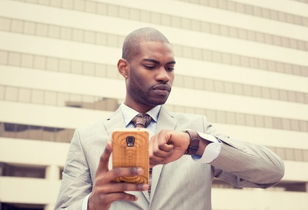 portrait young businessman texting on mobile phone and looking at his watch isolated on outdoor background of corporate building windows Stock Photo