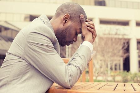 black tie: perfil lateral subray� el empresario joven sentado fuera de la oficina corporativa sosteniendo la cabeza con las manos mirando hacia abajo. Negativos emoci�n humana sentimientos de expresi�n facial.