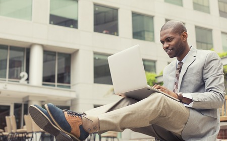 hombres negros: Feliz hombre de negocios joven hermoso que trabaja en la computadora portátil al aire libre en un fondo del edificio corporativo. Efecto de filtro de Instagram