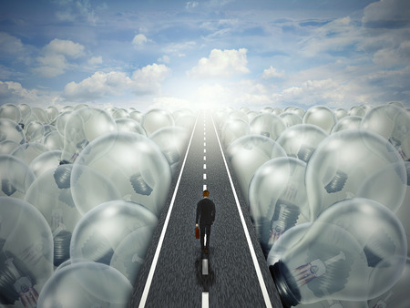 Idea road creative path business concept. Man walking down the street highway through a landscape of light bulbs. Symbol metaphor for innovation success brainstorming solution. Stock Photo