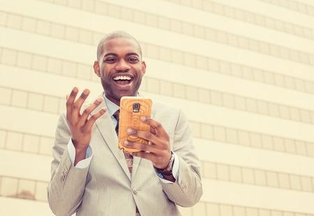 hombres negros: Hombre emocionado mirando a su teléfono inteligente lectura buena de correo electrónico mensaje de noticias Foto de archivo
