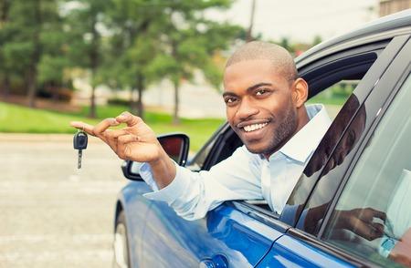 Nahaufnahmeporträt glücklich, lächelnd, junger Mann, Käufer, der in seinem neuen blauen Auto zeigt die Schlüssel lokalisiert außerhalb des Händlers, Verkaufsstellenlos, Büro sitzt. Persönlicher Transport, Autokaufkonzept Standard-Bild