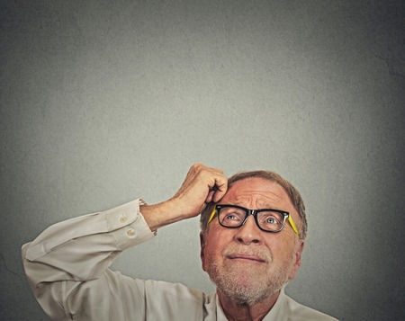 Closeup headshot undecided senior man with glasses scratching head thinking looking up isolated gray wall background with copy space. Human face expression emotion perception