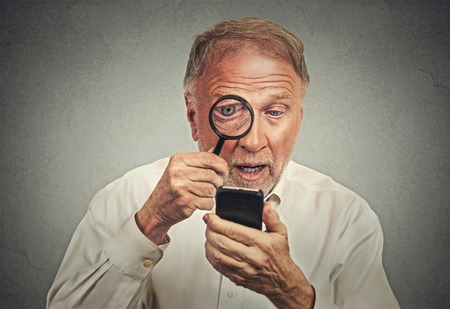 degeneration: Curious. Portrait senior man investigator looking through magnifying glass at smart phone isolated grey wall background. Human face expression. Security safety or bad vision concept Stock Photo