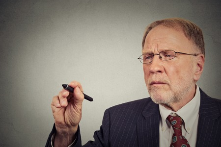 college professor: Closeup portrait businessman writing on a gray wall
