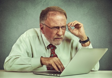 Closeup portrait senior elderly mature business man with glasses having eyesight problems confused with laptop software isolated gray background. Age related changes. technology and senior people