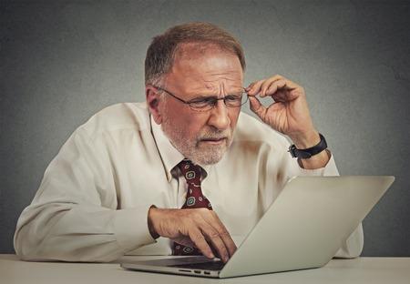 Closeup Portrait Senior älterer fälliger Geschäftsmann mit Brille mit Sehstörungen mit Laptop-Software isoliert grauen Hintergrund verwirrt. Altersbedingte Veränderungen. Technologie und ältere Leute