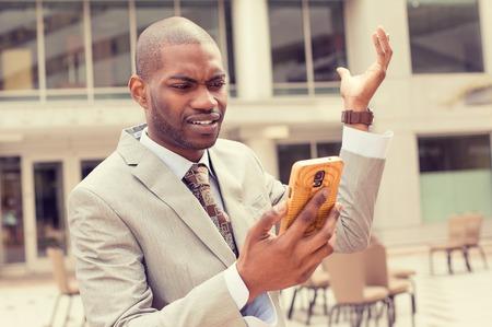 personne en colere: Gros plan malheureux jeune homme en costume parler textos sur téléphone portable à l'extérieur. Expression négative de visage humain