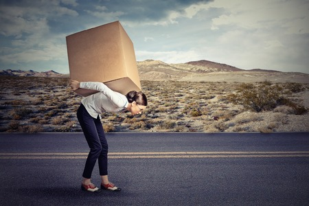 hard way: Woman carrying on her shoulders a large box