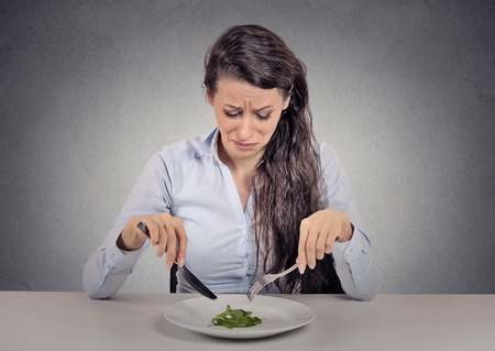 unhealthy diet: Young woman tired of diet restrictions eating green salad sitting at table isolated grey wall background. Human face expression emotion. Nutrition concept Stock Photo