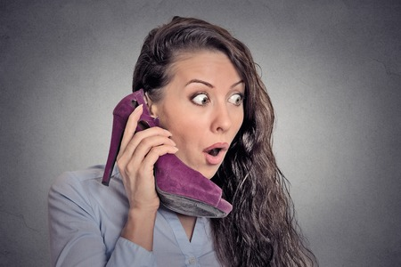 high heeled shoe: Headshot young surprised woman holding high heeled shoe in her hand as a phone isolated on grey wall background. human face expression emotion feelings reaction Stock Photo