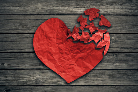 damaged: Broken heart breakup concept separation and divorce icon. Red crumpled paper shaped as a torn love on old wood symbol of medical cardiovascular health care problems due to illness Stock Photo