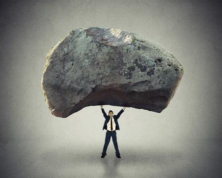 liderazgo: Poder de liderazgo con la capacidad de inspirar como hombre de negocios levantando una enorme roca quitando un gran obstáculo y predicar con el ejemplo, como un concepto de negocio de éxito y determinación.