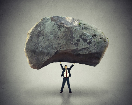 leadership: Power of leadership with the ability to inspire as a businessman lifting up a huge boulder removing a large obstacle and leading by example as a business concept of success and determination.
