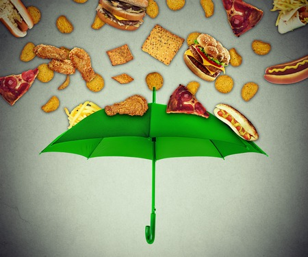 poor health: Bad diet protection food concept with group of greasy fatty fast food falling down like rain and green umbrella stopping unhealthy food as metaphor for poor nutrition eating habits