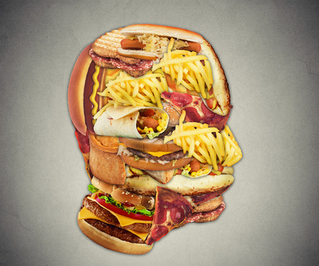 Unhealthy diet health concept with group of greasy fast food in shape of human head symbol of dangerous eating lifestyle and icon of addiction to bad nutrition and risk of heart disease.