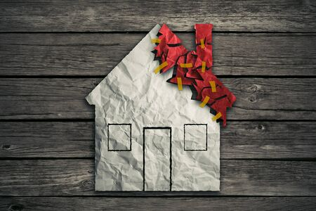 home expenses: Home repair concept and house improvement symbol as crumpled paper shaped as residential structure with torn pieces as icon for renovations maintenance. Stock Photo
