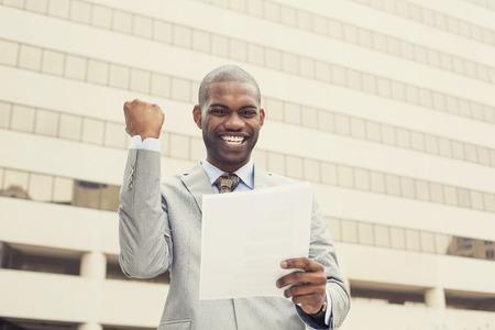 축하: 성공적인 젊은 전문적인 사람이 성공 신 계약 문서를 들고 기념. 기업가는 작업의 성공을 즐긴다.
