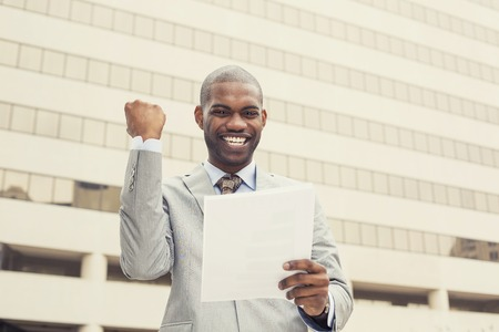 Hombre profesional joven acertado celebra éxito la celebración de nuevos documentos del contrato. Empresario goza de éxito en el trabajo.