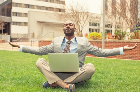 rest and relaxation: Young businessman with computer relaxing outside corporate office sitting on green grass in mediation mode Stock Photo