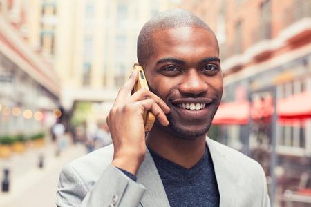 personen: Portret jonge stedelijke professionele lachende man met behulp van slimme telefoon praten over de mobiele buiten buitenshuis