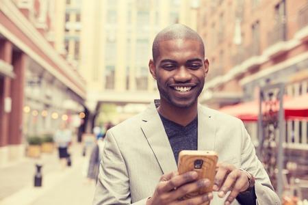 personnes: Jeune sourire heureux homme professionnel urbain utilisant un téléphone intelligent. Businessman holding mobile smartphone utilisant app textos sms un message portant la veste Banque d'images