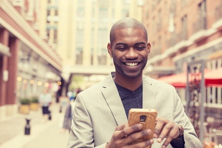 african business man: Young happy smiling urban professional man using smart phone. Businessman holding mobile smartphone using app texting sms message wearing jacket