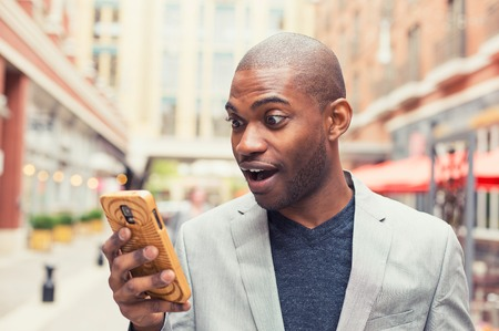 text: Young man using smart phone. Businessman holding mobile smartphone using app texting sms message wearing jacket