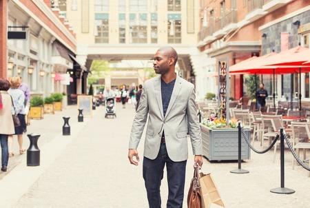 路上で歩いて買い物袋を持つ幸せな男