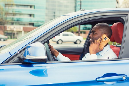 Young handsome businessman using mobile phone while driving car to work. Risky, reckless driver bad habits. Traffic safety rule violation lack of attention concept photo