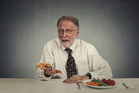 Sad man looking at pizza tired of salad diet Stock Photo