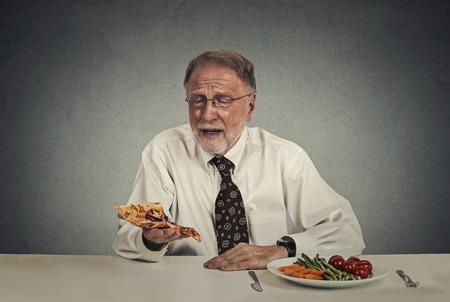 renunciation: Sad man looking at pizza tired of salad diet Stock Photo