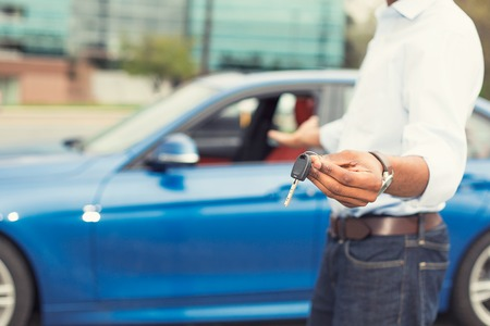 rent: Male hand holding car keys offering new blue car on background