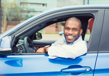 car salesperson: Closeup portrait happy smiling young man buyer sitting in his new car excited ready for trip isolated outside dealer dealership lot office. Personal transportation auto purchase concept
