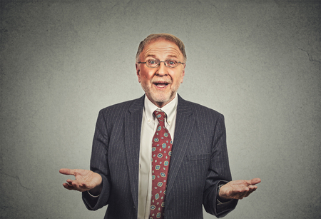 Closeup portrait clueless senior mature man, arms out asking why what\'s the problem who cares so what, I don\'t know. Isolated grey . Human emotion facial expression feeling body language