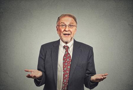 Closeup portrait senior mature man, bras tendus demandant pourquoi quel est le problème qui s'en soucie alors quoi, je ne sais pas. Gris isolé. Émotion humaine expression faciale sentiment langage corporel