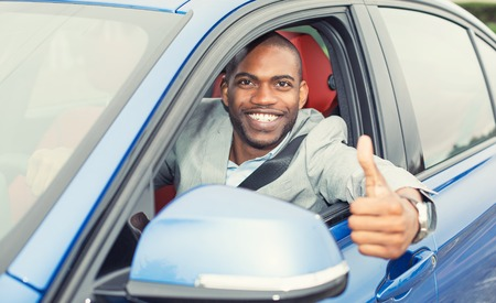 loans: Car. Man driver happy smiling showing thumbs up coming out of blue car side window on outside parking lot background. Young man happy with his new vehicle. Positive face expression Stock Photo