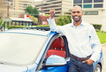 llaves: Hombre joven con las teclas de pie junto a su nuevo coche Foto de archivo