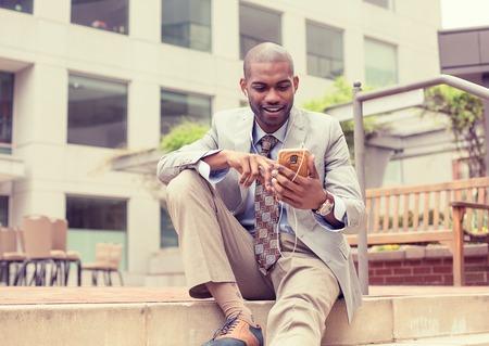 dia soleado: Retrato de un hombre feliz joven y sonriente escuchar música en el teléfono móvil sentado al aire libre en un día soleado. Positivo expresión de la cara