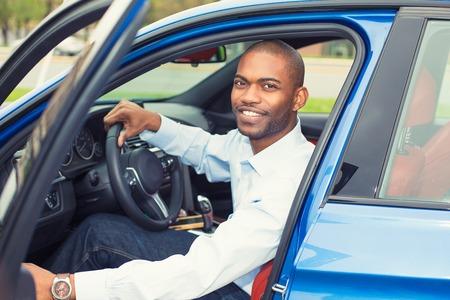 Gelukkige knappe man in zijn nieuwe blauwe auto Stockfoto