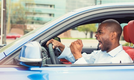 pissed off: Portrait displeased angry pissed off aggressive man driving car, shouting at someone in traffic hand fist up in air side door view. Emotional intelligence concept. Negative human expression