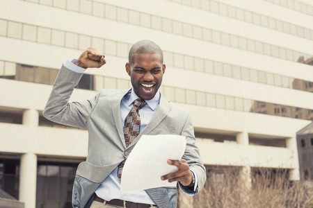 new contract: Successful young professional man celebrates success holding new contract documents. Entrepreneur enjoys success in job.