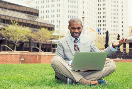 outdoor reading: A smiling man with laptop outdoor reading good news email Stock Photo