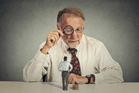 face expression: Curious corporate businessman skeptically meeting looking through magnifying glass at small employee standing on table isolated grey office wall background. Human face expression attitude perception Stock Photo