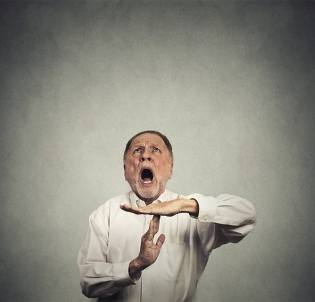 errands: Elderly man boss showing time out hand gesture, frustrated screaming to stop looking up isolated on grey wall background. Too many things to do. Human emotions face expression reaction