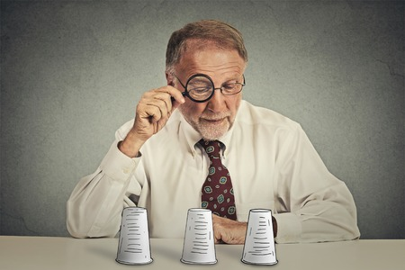 conjuring: Portrait senior elderly  business man with glasses sitting at table desk looking through magnifying glass wondering playing conjuring trick game isolated grey wall background. Gambling risk concept Stock Photo