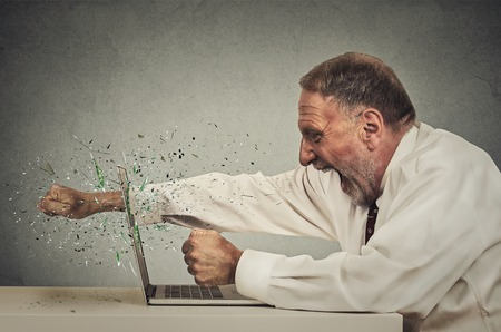 anger management: furious senior businessman throws punch into computer screaming isolated grey office wall background. Negative human emotions, facial expressions, feelings, aggression, anger management issues concept