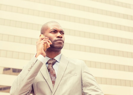 black professional: Closeup headshot handsome young businessman talking on mobile phone outdoors. Stock Photo